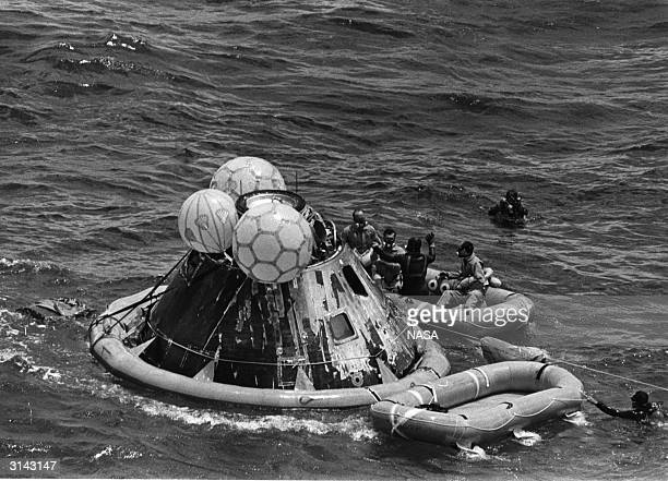 A US Navy rescue crew member with the Apollo 12 astronauts Charles 'Pete' Conrad Jr Richard F Gordon Jr and Alan L Bean in a life raft during...