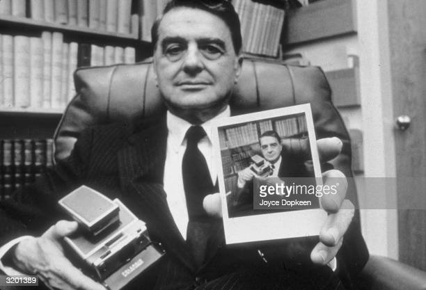 Portrait of Dr H Edwin Land President and Director of the Polaroid Corporation holding a portrait of himself posing with the Sx70 Polaroid camera in...