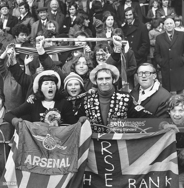 An Arsenal football club supporter holding a union jack and wearing a jacket festooned with badges with other fans during a match