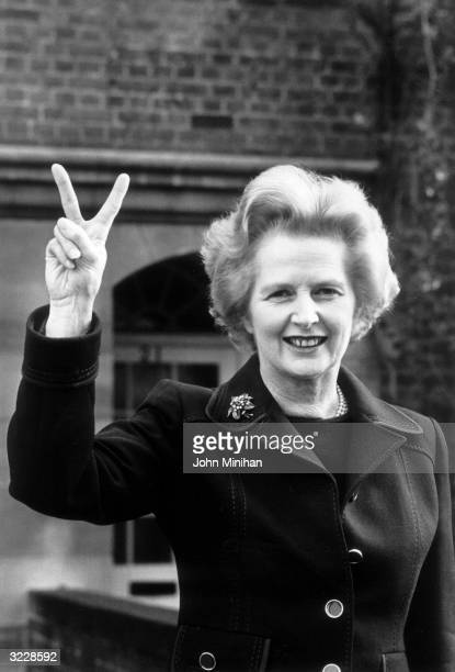 Conservative party leader Margaret Thatcher makes a 'victory' sign outside her home in Chelsea London
