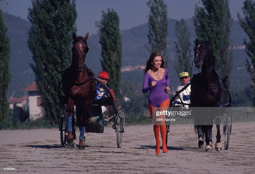 Marie-Louise Scio in leotard and tights running between two racing sulkies in the health resort of Montecatini, Italy. She is the American wife of Baron Scio, Italian businessman, developer and hotel owner.