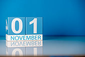 November 1st. Day 1 of last autumn month, calendar on blue background. Empty space for text.