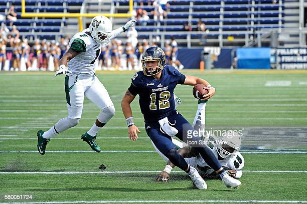 FIU quarterback Alex McGough evades Charlotte defensive lineman Larry Ogunjobi while carrying the ball in the first quarter as the FIU Golden...