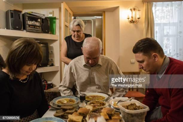 Tatyana Kravchenko Alexey and Lyubov Koptev and Ivan Belenko a spokesman of Jehowah's Witnesses in St Petersburg pray before dinner in Koptevs' house...