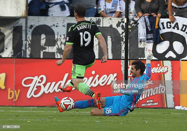 Los Angeles Galaxy goalkeeper Jaime Penedo makes a sliding save over Seattle Sounders FC forward Chad Barrett during the game at the Stub Hub Center...