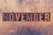 The word November concept and theme written in vintage wooden letterpress type on a grunge background.