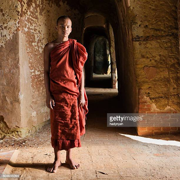 Novice Buddhist monk standing inside the temple