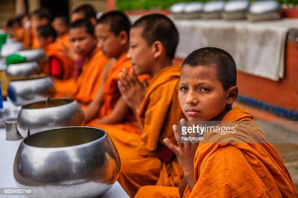 Novice Buddhist monks eating together in monastery, Bhaktapur