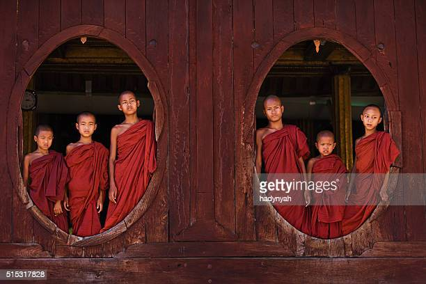 Novice Buddhist monks posing in the window of monastery