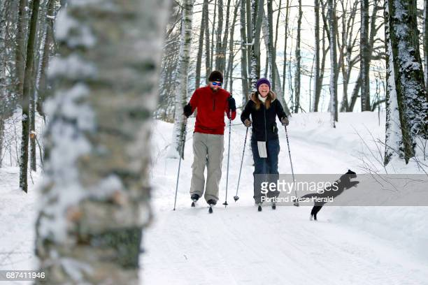 Novice crosscountry skiers Tom and Coni of Bolton Massachusetts share a laugh Saturday at Smiling Hill Farm as a resident cat leaps from the trail