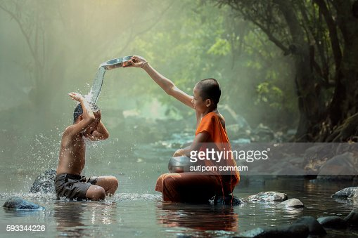 Novice monk playing water splash with the boy