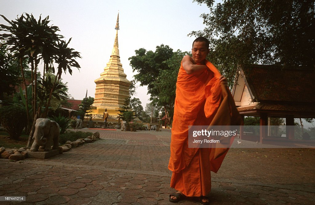 Novice monk Sanya Insuan wraps himself in his robes before leaving the grounds of Wat Doi Thong temple to study at another temple, in Chiang Rai. In the background is a gold-covered Chedi which is believed to hold a relic of the Buddha..