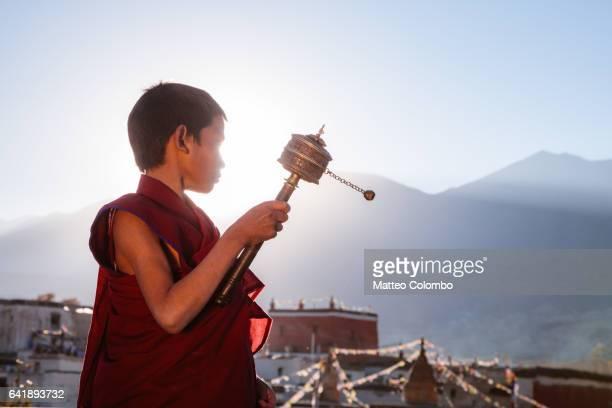 Novice monk spinning prayer wheel, Upper Mustang, Nepal