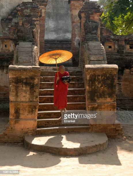 Novice monk with parasol walking down the stairs