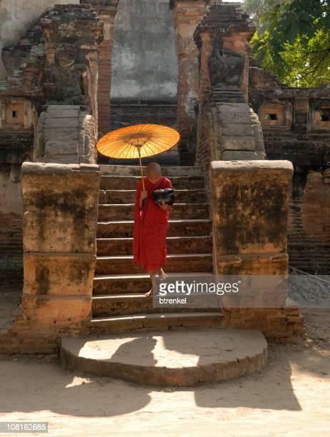 Buddhistischer Mönch mit Sonnenschirm zu Fuß die Treppe hinunter