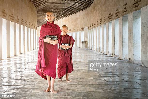 Novice Monks Walking with Alms Bowls Monastery Archway Myanmar