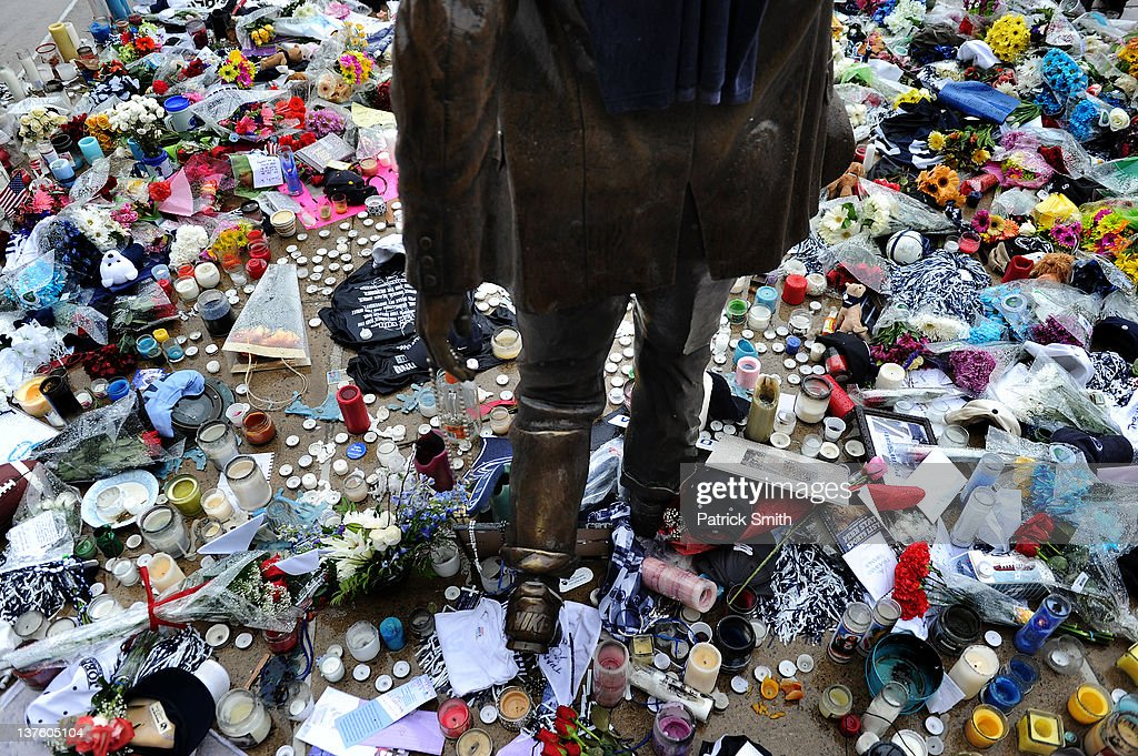 Now a make-shift memorial, candles, newspapers, t-shirts, and other gifts line the ground of the statue of Joe Paterno, the former Penn State football coach who died yesterday, outside Beaver Stadium on the campus of Penn State on January 23, 2012 in State College, Pennsylvania. Paterno, who was 85, died due to complications from lung cancer on January 22, 2012.