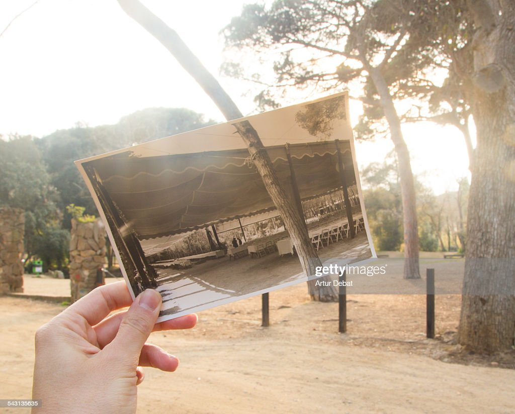 Now and then, holding picture by hand on park.