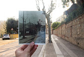 Now and then, holding picture by hand on street.