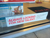 Now Hiring sign in the window of GNC at Jacksonville Beach Florida USA on October 26 2014