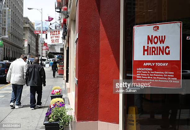 A 'now hiring' sign is posted in the window of a fast food restaurant on July 8 2016 in San Francisco California According to the the US Labor...