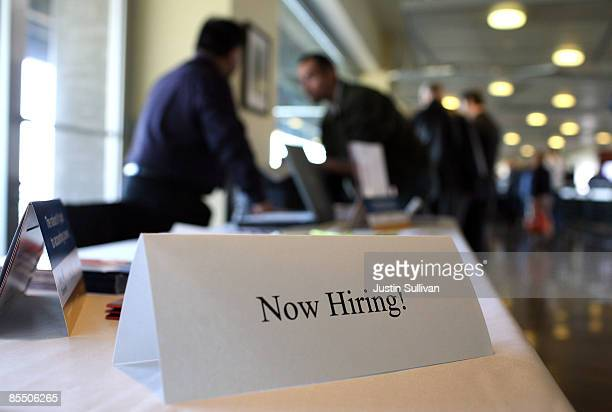 A 'now hiring' sign is posted on a table during the Recruit Military Career Fair March 19 2009 at ATT Park in San Francisco California Hundreds of...