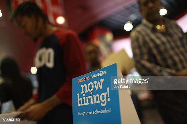 A 'now hiring' sign is seen at the Toys'R'Us booth during the JobNewsUSA job fair at the BBT Center on November 15 2016 in Sunrise Florida Over 30...