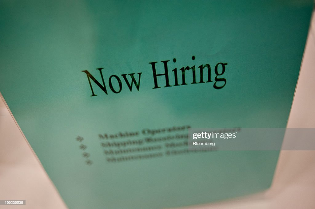 A 'Now Hiring' sign sits on an employer's table during a job fair at Illinois Valley Community College (IVCC) in Oglesby, Illinois, U.S., on Wednesday, April 10, 2013. The U.S. Department of Labor is scheduled to release jobless claims figures on April 11. Photographer: Daniel Acker/Bloomberg via Getty Images