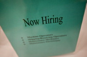 A 'Now Hiring' sign sits on an employer's table during a job fair at Illinois Valley Community College in Oglesby Illinois US on Wednesday April 10...