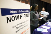 A 'Now Hiring' sign stands at one of the exhibitors tables at the Columbus Career Fair in Columbus Ohio US on Thursday Dec 5 2013 Applications for US...
