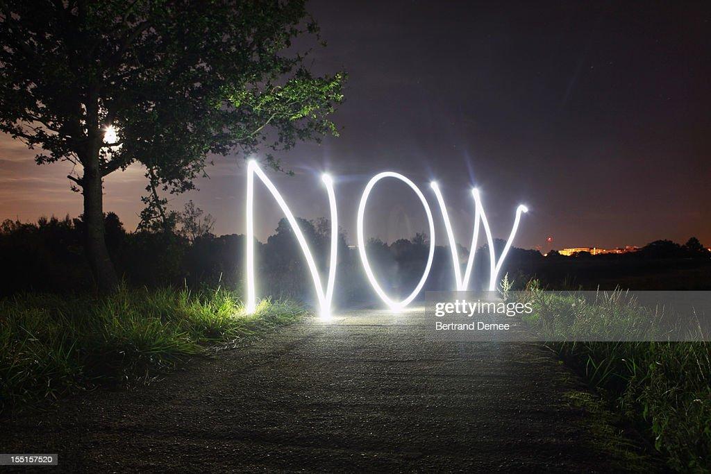 'Now' written in light