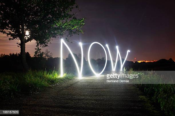 'Now' written in light