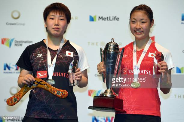Nozomi Okuhara of Japan holds the winner's trophy after defeating compatriot Akane Yamaguchi in the Australian Open women's singles badminton final...