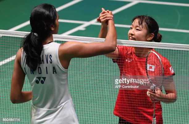 Nozomi Okuhara of Japan shakes hands with Pusarla V Sindhu of India after winning their women's singles second round match at the Japan Open...