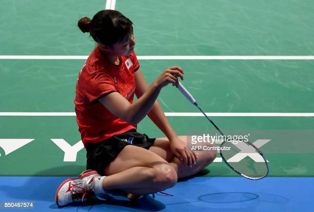 Nozomi Okuhara of Japan sits on the floor during her women's singles second round match against Pusarla V Sindhu of India at the Japan Open Badminton...