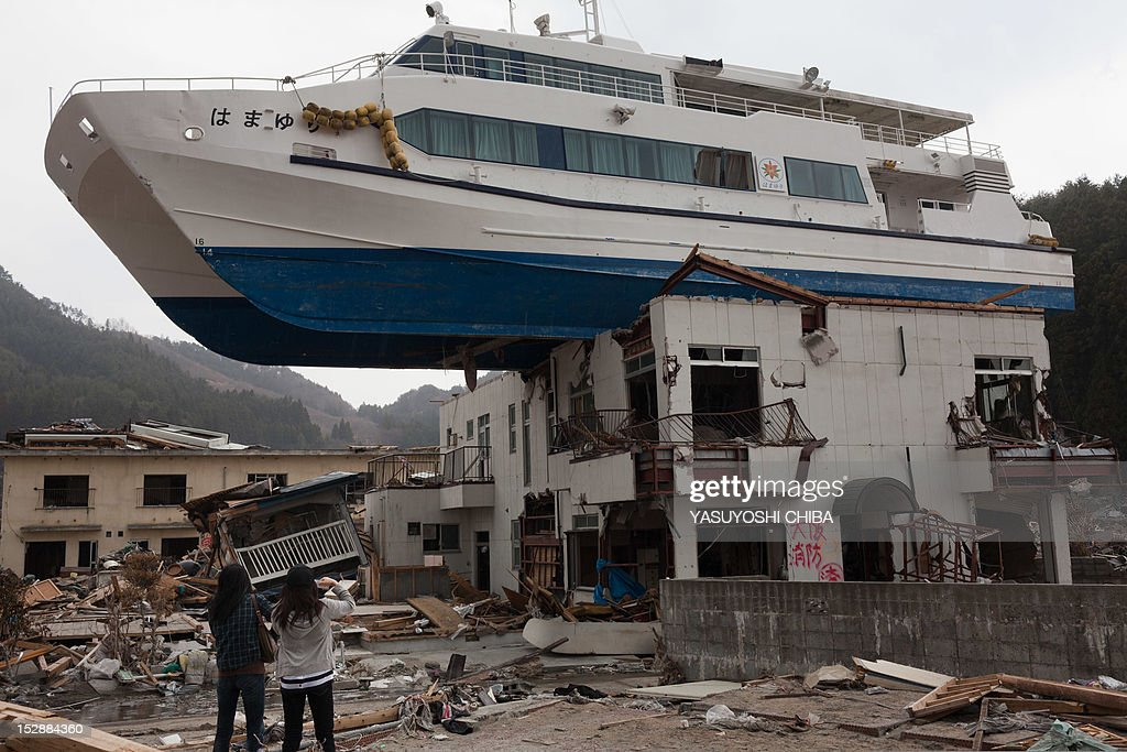 Nozomi Sabanai together with her sister looks at catamaran sightseeing boat that was thrown by the tsunami onto a two story building at Otsuchi town...
