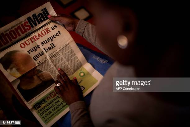 Nthabiseng Mabuza holds a copy of Kathorus Mail a local newspaper that was published in 2014 with a blurred image of her face on the front cover as...