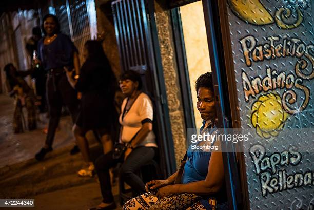 NuBia Asprilla from Cali Colombia right sits outside a bar in the Petare neighborhood on the outskirts of Caracas Venezuela on Saturday April 25 2015...