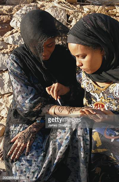 Nubian women's wedding preparations, one decorating another's hands