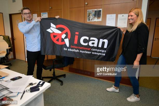 Nuclear disarmament group ICAN executive director Beatrice Fihn and coordinator Daniel Hogsta hold a banner with their logo after ICAN won the Nobel...