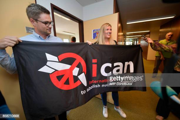 Nuclear disarmament group ICAN executive director Beatrice Fihn and coordinator Daniel Hogsta hold a banner with the group's logo after ICAN won the...