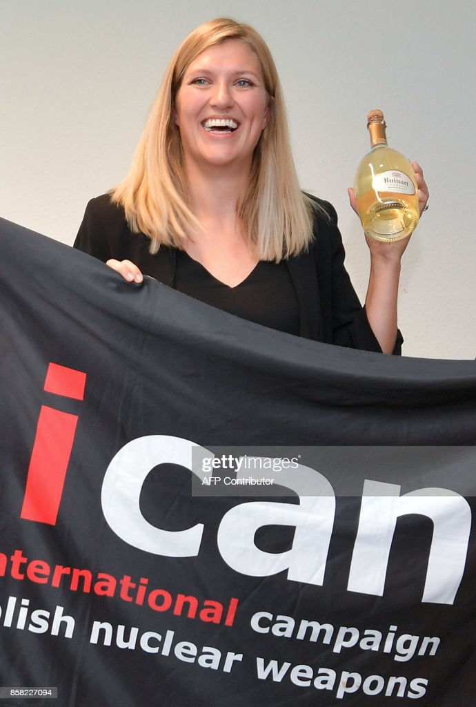 Nuclear disarmament group ICAN executive director Beatrice Fihn holds a banner with the group's logo after ICAN won the Nobel Peace Prize for its decade-long campaign to rid the world of the atomic bomb as nuclear-fuelled crises swirl over North Korea and Iran, on October 6, 2017 in Geneva. With the nuclear threat at its most acute in decades, the International Campaign to Abolish Nuclear Weapons, which on October 6 won the Nobel Peace Prize, is urgently pressing to consign the bomb to history. / AFP PHOTO / Fabrice COFFRINI