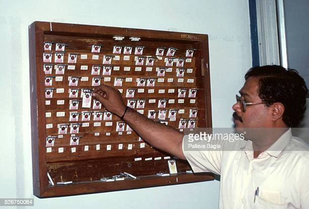 A nuclear engineer places his radiation detection badge on shelf that holds all other badges These badges are worn when entering the Kalpakkam...