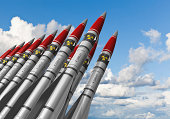 Row of heavy nuclear missiles against blue sky with clouds. See also: