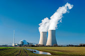 Nuclear power station countryside with two steaming cooling towers and blue sky.