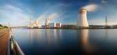 Daytime long exposure shot of a nuclear power plant at a river with blue sky and some clouds as well as blurred reflection. The rather old plant is located in Tihange, Belgium.  [url=http://www.michae