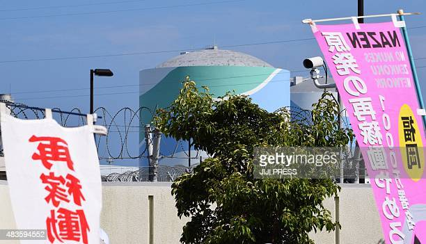 A nuclear reactor building of the Kyushu Electric Power Sendai nuclear power plant is seen between banners against the restarting of the nuclear...