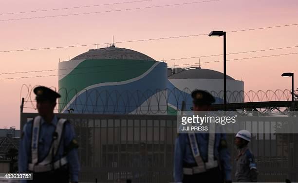 Nuclear reactor buildings of the Kyushu Electric Power Sendai nuclear power plant are seen behind police officers standing guard in the twilight in...