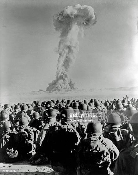 Nuclear test at Frenchman's Flat November 1951 Members of 11th Airborne Division kneel on ground as they watch mushroom cloud of atomic bomb test...