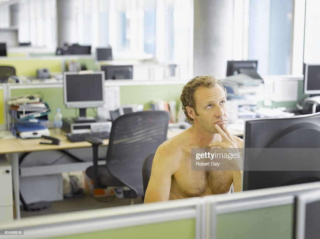 Nude businessman sitting at desk : Stock Photo